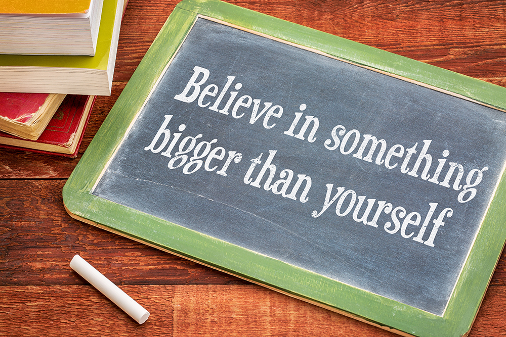 Believe in something bigger than yourself - inspirational text on a slate blackboard with a white chalk and a stack of books against rustic wooden table