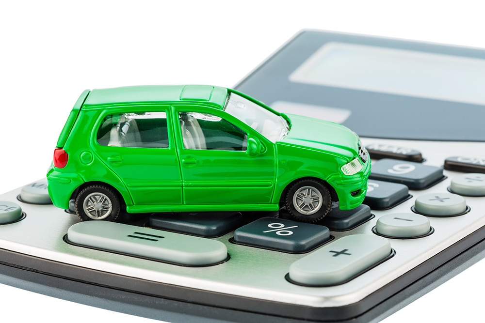 a car is on a calculator. cost of gasoline, wear and insurance.