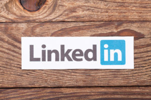Linkedin logo sign printed paper and placed on wood background.